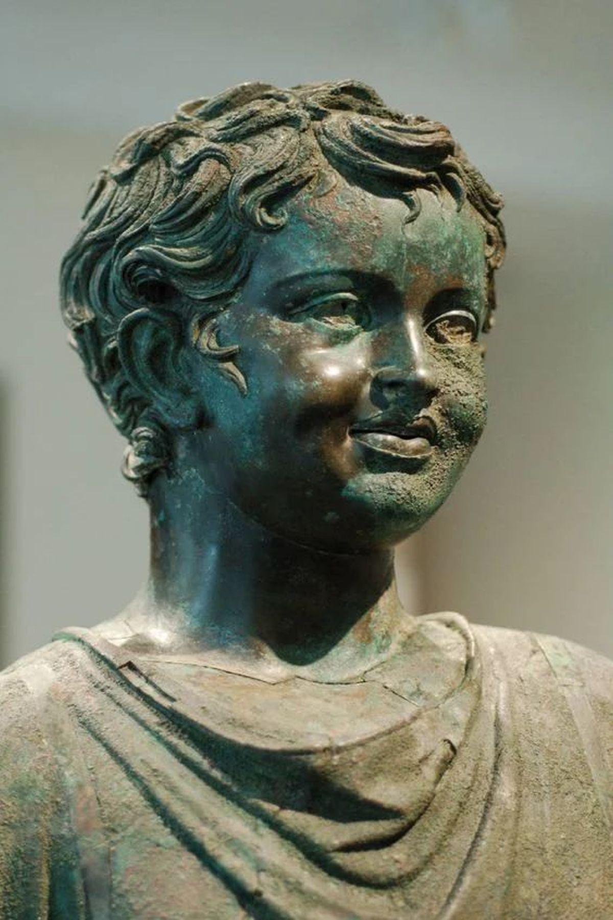 Rzeźba rzymska ukazująca uśmiechniętego chłopca.   romancoins.info