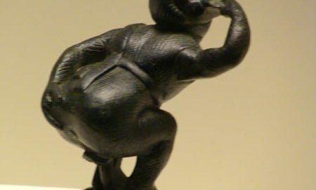 A bronze statuette depicting a comic actor