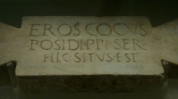 The epitaph on the stele reads: Here lies Eros, the cook of Posidippus, a slave.