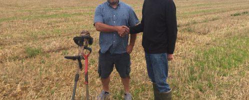 Historyk Mike Smale podaje rękę właścicielowi ziemi, na której znaleziono setki rzymskich denarów.