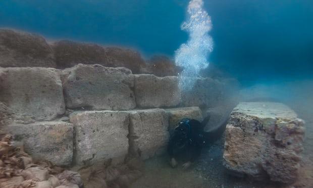 Archeolog nurkujący wśród pozostałości portu w Koryncie