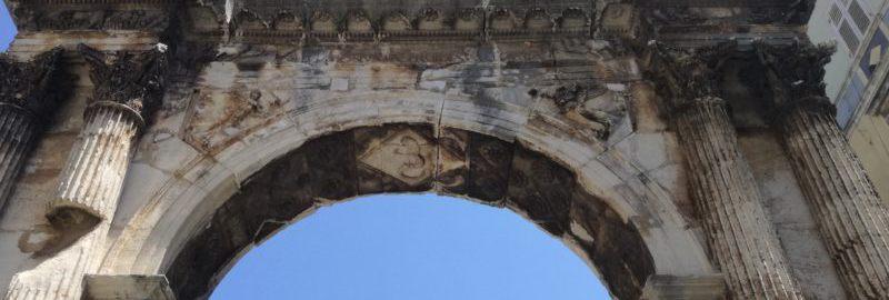 Attyka łuku triumfalnego w Puli z widocznymi bazami posągów.