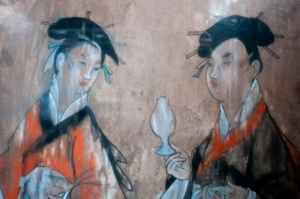 Wall painting of two women in silk robes. The painting comes from the tomb of Dahuting, from the late Eastern Han dynasty (25-220 CE), in Zhengzhou, China.